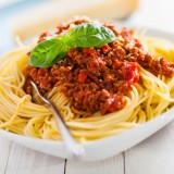 Bowl of delicious Italian spaghetti Bolognese topped with a rich meat and tomato sauce and sprinkled with grated parmesan cheese with a wedge behind