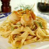 Fettucini with caramelized lemon and dill sea scallops in a table setting.